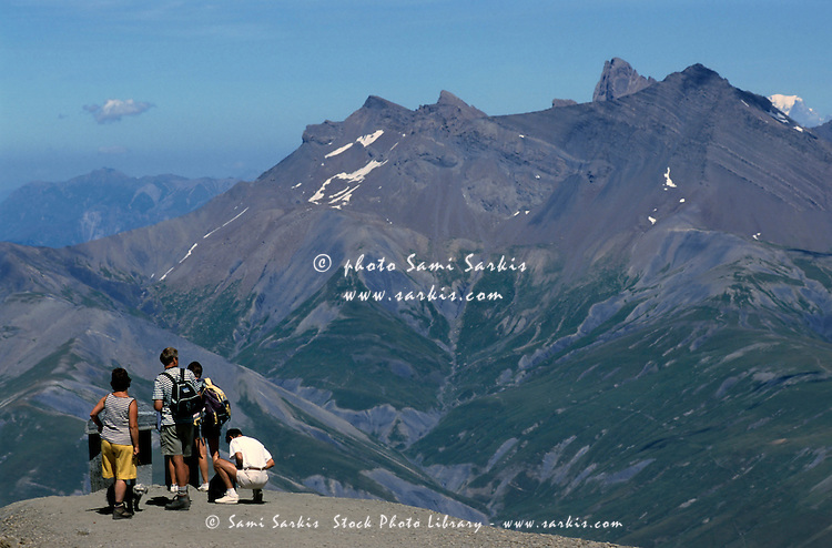 Group of tourists on Ruillans Pass look out at the majestic French Alps, France.