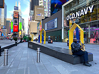 New York, New York City. New Yorkers are told to stay home during the corona virus, (COVID-19) so New York has become eerily empty.  Times Square is devoid of its usual crowds. Sweet Lou pays his sax to an empty street.