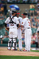 Rochester Red Wings pitching coach Stu Cliburn (33) talks with starting pitcher Jose Berrios (16) as catcher John Ryan Murphy (12) listens in during a game against the Indianapolis Indians on May 26, 2016 at Frontier Field in Rochester, New York.  Indianapolis defeated Rochester 5-2.  (Mike Janes/Four Seam Images)