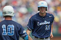 North Carolina shortstop Landon Lassiter (12) is greeted by teammate Brian Holberton (10) against the Louisiana State Tigers during Game 7 of the 2013 Men's College World Series on June 18, 2013 at TD Ameritrade Park in Omaha, Nebraska. The Tar Heels defeated the Tigers 4-2, eliminating LSU from the tournament. (Andrew Woolley/Four Seam Images)