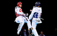 04 DEC 2011 - LONDON, GBR - Aaron Cook (GBR) (on left, in red) launches an attack on Nicolas Garcia (ESP) (on right, in blue) during their men's -80kg category semi final contest at the London International Taekwondo Invitational and 2012 Olympic Games test event at the ExCel Exhibition Centre in London, Great Britain .(PHOTO (C) NIGEL FARROW)