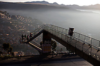 A man walks on top of a bridge early morning on the main highway from La Paz to El Alto.Just 25 years ago it was a small group of houses around La Paz  airport, at an altitude of 12,000 feet. Now El Alto city  has  nearly one million people, surpassing even the capital of Bolivia, and it is the city of Latin America that grew faster .<br /> 	It is also a paradigmatic city of the tubles and traumas of the country. There got refugee thousands of miners that lost  their jobs in 90 ´s after the privatization and closure of many mines. The peasants expelled by the lack of land or low prices for their production. Also many who did not want to live in regions where coca  growers and the Army  faced with violence.<br /> 	In short, anyone who did not have anything at all and was looking for a place to survive ended up in El Alto.