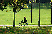A mother pushes her child in a buggy in Paddington Recreation Ground, managed by Westminster City Council.