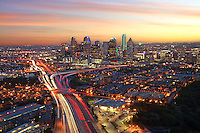 The warmth of the evening sunlight cascades onto downtown Dallas, covering the cityscape in a placid warm glow. As cars hum along the North Central Expressway, red and white lights from vehicle traffic streak through the city creating a sense of movement, energy, and depth. This image was taken from the roof of Cityplace Tower, the tallest building outside of downtown Dallas.