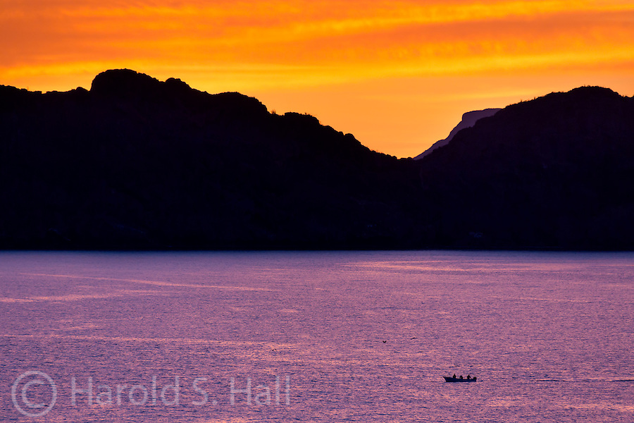 Sunrise near San Carlos, Mexico casts a purple glow on the water while a single fishing boat arrives on the scene for yet another hopeful day on the Sea of Cortez.