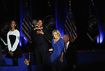 President Barack Obama joined on stage by his daughter Malia receives a hug from his wife, First Lady Michelle Obama, as Vice-President Joe Biden's wife Jill and Biden enter the stage after President Obama gave his farewell address to a crowd of thousands and the nation during his farewell address at McCormick Place in Chicago, Illinois on January 10, 2017.