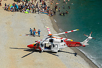 BNPS.co.uk (01202 558833)<br /> Pic: Graham Hunt/BNPS<br /> <br /> The coastguard helicopter lands on the beach at Durdle Door in Dorset to deal with a medical emergency on an afternoon of scorching hot sunshine and clear blue skies.<br /> <br /> Sunbather and visitors have been cleared from a stretch of the beach so the helicopter could land.
