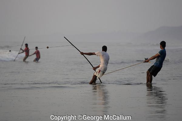 Beach fishermen pulling Gill net through surf, Goa, Arabian sea, India