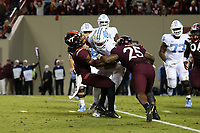 BLACKSBURG, VA - OCTOBER 19: Sam Howell #7 of the University of North Carolina is tackled by Khalil Adler #9 and Rayshard Ashby #25 of Virginia Tech during the sixth overtime during a game between North Carolina and Virginia Tech at Lane Stadium on October 19, 2019 in Blacksburg, Virginia.