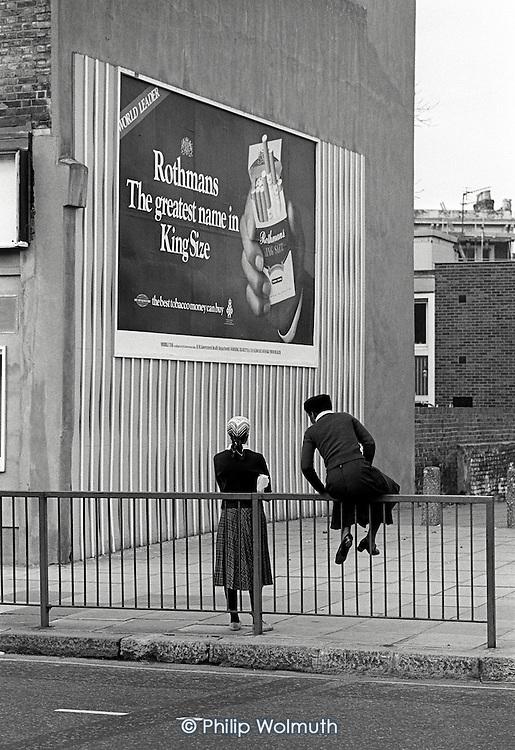 Two teenage girls and a cigarette advertisement, Harrow Road, North Paddington, London.