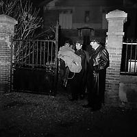 Devant la villa au 19 bis place Armand Leygue. Nuit du 18 au 19 décembre 1972. Vue d'ensemble des policiers sortant le corps d'une des victime de la propriété : au 1er plan un policiers tient un corps enroulé dans un drap (certainement celui de la fillette), est en train de passer le portail ; en arrière-plan façade de la villa. Vue de nuit. Cliché pris après la découverte du meurtre d'une jeune femme et de sa fille dans cette villa. Observation: Double crime de la place Armand Leygue : le 18 décembre 1972, en fin d'après-midi, M. René Delamare découvre le cadavre de sa femme Monique et de sa fille de 4 ans Catherine dans la chambre à coucher au rez-de-chaussée du 19 bis Place Armand-Leygue. Les deux victimes ont été tuées de plusieurs coups de couteau. Très rapidement suspect n°1, le mari avoue le double crime le 18 décembre 1972.