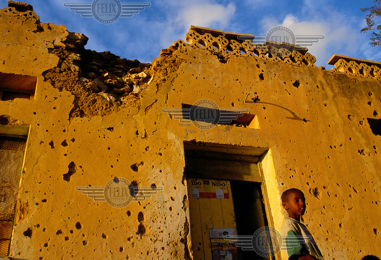 A child stands outside his house that is pitted with bullet holes from the battle for Hargeisa, the capital of Self Declared Independent country of Somaliland.