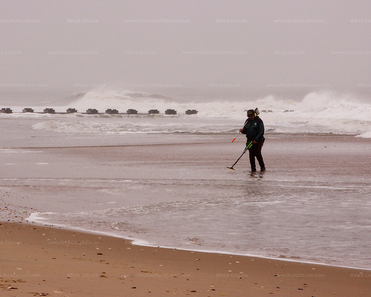 As the storm begins to clear, beachcombers wielding modern technology flock to the beaches at Rehobboth Beach, Delaware, hoping for finds turned up by the massive churn of a nor'easter in November 2009.