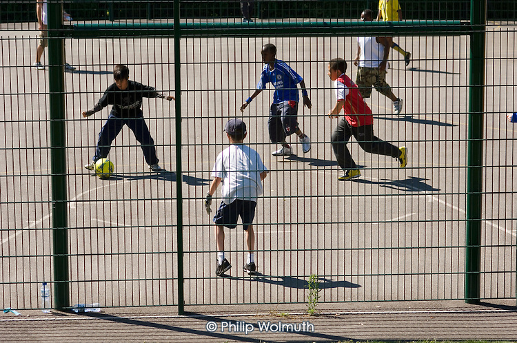 Boys playing football in Queens Park Gardens, a Westminster City Council park.