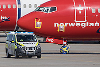 "A police car drives on the tarmac in front of aircraft ""mothballed"" as they are grounded due to the coronoa crisis. <br /> <br /> Norwegian authorites introduced measures to combat the Coronavirus (COVID-19)  leaving Gardermoen Airport, near the Norwegian capital Oslo, deserted. <br /> <br /> Restriction on public gatherings and travel have grounded most airplanes, and stopped nearly all domestic and foreign travel. <br /> <br />  Like most capitals, Oslo is usually busy on a Saturday night. But on the first weekend after Norwegian authorites introduced measures to combat the Coronavirus (COVID-19) the city was almost deserted. <br /> <br /> Restriction on public gatherings, closure of schhols, new rules for those serving food and drinks, and fear of further spread of the virus compelled most bars and restaurants to close. <br /> <br /> 28,5 million passangers used the airport in 2018, with the airline Norwegian flying the most people. At teh time of writing Norweigan is on the verge of bankruptcy, and hoping to get governemnt aid to surive the economic crisis caused by the corona virus.  <br /> <br /> <br /> ©Fredrik Naumann/Felix Features"