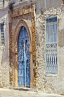 Tunisia, Sidi Bou Said.  Door and Stone Arch as Door Frame.  This is a poor house--door not freshly painted, stucco not well maintained.