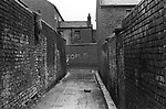 Inner city young boy climbing down a very high wall into the back alley. Belfast Northern Ireland UK. 1970