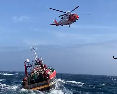 The fishing vessel and the Coastguard Rescue 117 Helicopter, as the heli crew drop the emergency salvage pumps and winchman on board the trawler in heavy seas.  The Courtmacsherry RNLI lifeboat stood by=
