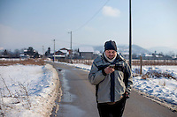Elvis Causevic checking his mobile phone on a road near the Sarajevo Tunnel museum. <br /> <br /> In 1992 while volunteering at the Varazdin refugee camp Panos photographer Bjoern Steinz met and became close to Elvis, a Bosnian Muslim refugee, and his family. They shared the hardships of camp life together which Steinz documented. While the prints were archived for many years two of the images always returned to Bjoern's thoughts. 25 years later he set out to try and find out what had happened to Elvis and his family in the intervening years. Modern social media made the task surprisingly easy and they were reunited in Hadzici where Elvis now lives with his family.