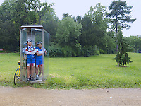 France. Paris. Bois de Boulougne. A group of four racing cyclists, all from asian ethnicity, stand inside a public phone booth. They protect themselves from the pouring rain. 06.06.10 © 2010  Didier Ruef