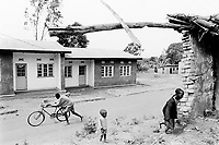 Burundi. Karuzi Province. Buhiga. Village's daily life. Teenage boy pushes his bicycle on the main dirt road. He walks near two modern concrete houses with metal sheets roofs. Children play by a destroyed brick wall.  © 2000 Didier Ruef