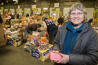 Longtime volunteer coordinator of the Iditarod People Food, Pat Owens, overseas the group of volunteers as they  sort and pack human food for the volunteers which will be working at the 20+ checkpoints durinig this year's 2016 Iditarod Race at the Airland Transport warehouse in Anchorage on Friday, February 19, 2016.