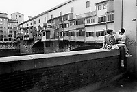 """Italy. Tuscany Region. Florence. A lovely teenage couple hugs and sits on a wall near the Ponte Vecchio. The man is making an obscene gesture with his right arm which meaning is """"vaffanculo"""" (Fuck off! Get lost!). The Ponte Vecchio (""""Old Bridge"""") is a Medieval stone closed-spandrel segmental arch bridge over the Arno River, noted for still having shops built along it, as was once common. Butchers initially occupied the shops; the present tenants are jewelers, art dealers and souvenir sellers. Florence is the capital city of the Italian region of Tuscany and of the province of Florence. © 1993 Didier Ruef"""