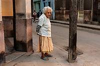 Elderly woman on Havana street corner, two school boys in background.