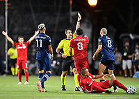 LAKE BUENA VISTA, FL - JULY 26: Referee Alex Chillowicz shows a yellow card to Alexander Ring of New York City FC as Valentín Castellanos of New York City FC and Marco Delgado of Toronto FC look on during a game between New York City FC and Toronto FC at ESPN Wide World of Sports on July 26, 2020 in Lake Buena Vista, Florida.