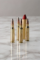 Bullets and lipstick on marble surface<br />