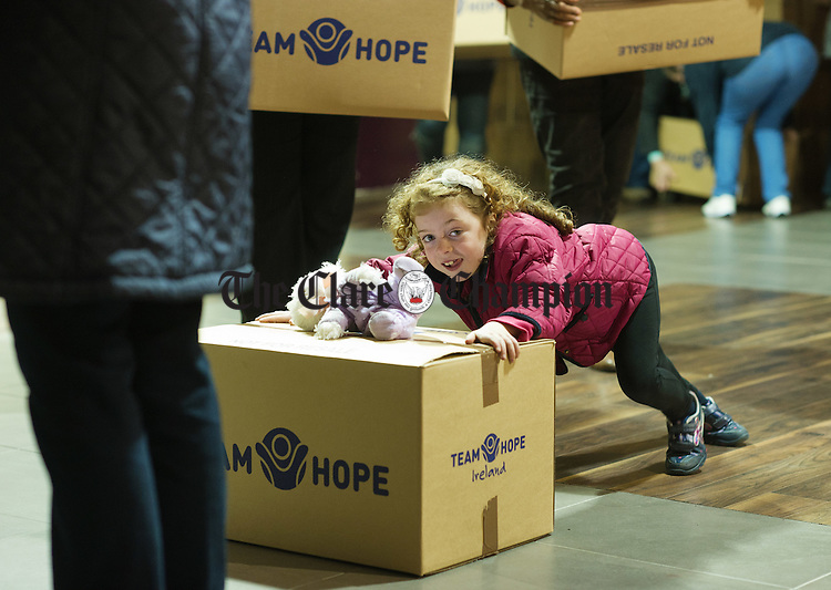 Young Nicole O Loughlin gives of her best as she joins other volunteers loading a truck with over 4000 Shoe boxes filled with Christmas presents for children in Eastern Europe as part of the annual Team Hope Christmas Shoebox Appeal. Photograph by John Kelly.