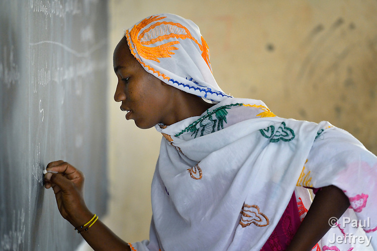 A girl writes on the blackboard during a class in the Bahadon Second Cycle School in Timbuktu, a city in northern Mali which was seized by Islamist fighters in 2012 and then liberated by French and Malian soldiers in early 2013. The jihadis first banned all schools, then under pressure from the community, allowed them to open but with separate classes for boys and girls.