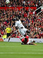 Pictured: Bafetimbi Gomis of Swansea (TOP) against Tyler Blackett of Manchester United. Saturday 16 August 2014<br /> Re: Premier League Manchester United v Swansea City FC at the Old Trafford, Manchester, UK.