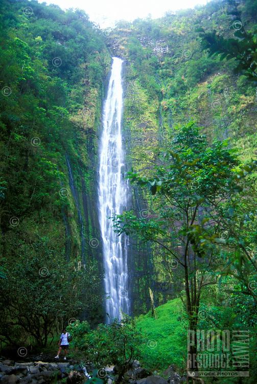 Hiker at the base of beautiful waterfall enjoying the view near Hana Maui in Haleakala National park.