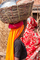 Abhaneri, Rajasthan, India.  Woman Carrying Cooking and Eating Utensils in a Basket on her Head.