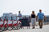 WEATHER PICTURE WALES<br /> Pictured: A man and women walk down the seafront in Mumbles, near Swansea, Wales, UK. Thursday 22 July 2021<br /> Re: High temperatures and sunshine has been forecast for most of the UK.