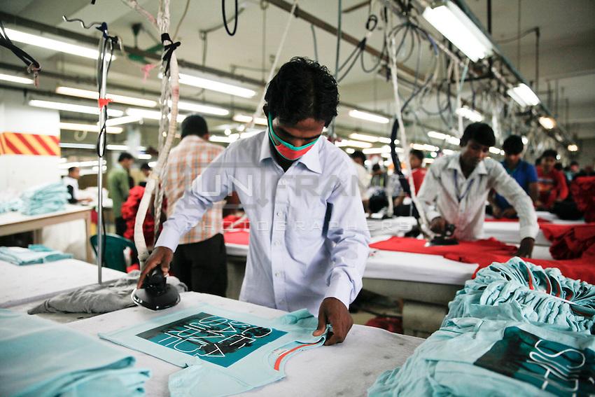 Before packaging the garments product, a Bangladeshi worker iron of the T-Shirts. gazipur, near Dhaka, Bnagladesh