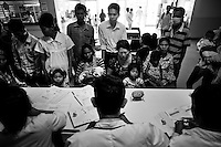 Crowded reception room - a typical scene for Cambodian hospitals. Parents and their diseased children waiting in line for their turn.