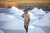 Salt mounds, salt processed by the evaporation of seawater (sea salt) -   elderly man at hard work, northeastern Brazil, Rio Grande do Norte State.