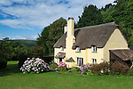 Great Britain, England, Somerset, Selworthy: Exmoor National Park. Traditional thatched cottage with Exmoor in distance | Grossbritannien, England, Somerset, Selworthy: Exmoor National Park, traditionelles Landhaus mit Reetdach