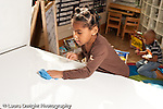 Education preschool 3-4 year olds clean up time girl using sponge to wipe table horizontal