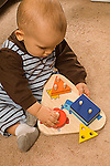 13 month old toddler boy sitting playing with peg puzzle holding peg in pincer grasp