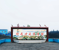 A wall mural showing the Great Wall of China near a factory site in Shanxi Province.