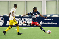 FOXBOROUGH, MA - MAY 16: DeJuan Jones #24 of New England Revolution passes under pressure from Harrison Afful #25 Columbus SC during a game between Columbus SC and New England Revolution at Gillette Stadium on May 16, 2021 in Foxborough, Massachusetts.
