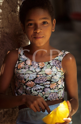 Recife, Brazil. Smiling mulata young woman holding a yellow fruit.