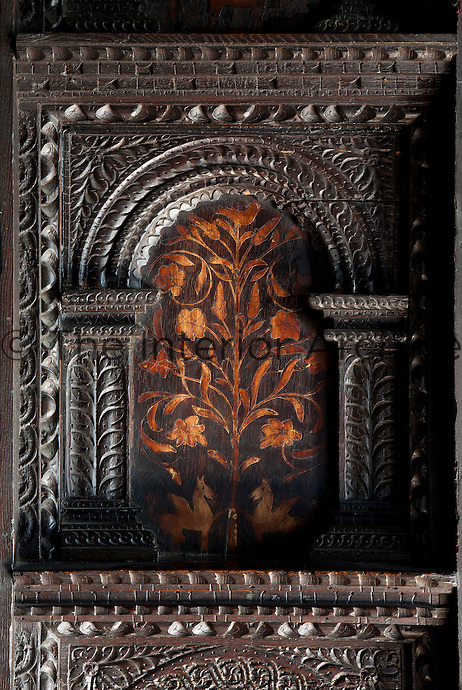 Detail of one of the carved oak panels with inlaid flower decoration in the Elizabethan dining room