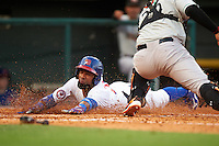 Buffalo Bisons shortstop Alexi Casilla (12) slides into home as catcher catcher Francisco Pena (29) swipes the tag during a game against the Norfolk Tides on July 18, 2016 at Coca-Cola Field in Buffalo, New York.  Norfolk defeated Buffalo 11-8.  (Mike Janes/Four Seam Images)