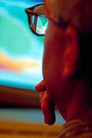 Technician looking at seismic data on computer screen, reflection in glasses