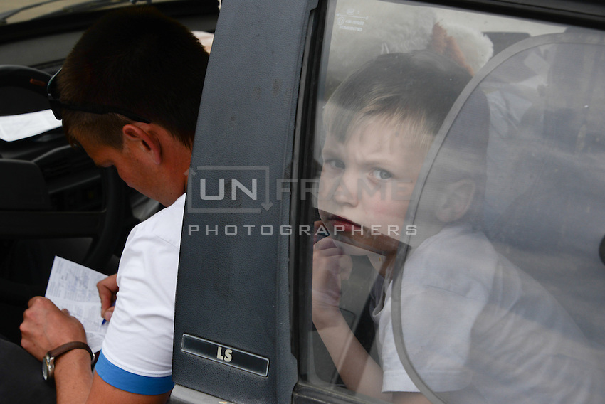 A familly in their car filling expatriation documents waiting inline at the border between Ukraine and Russia at Izvarine check point - one of border crossings controlled by Luhansk Peoples Republic. According to rebels around 5 thousand people leave Ukraine every day through Izvarine border crossing.
