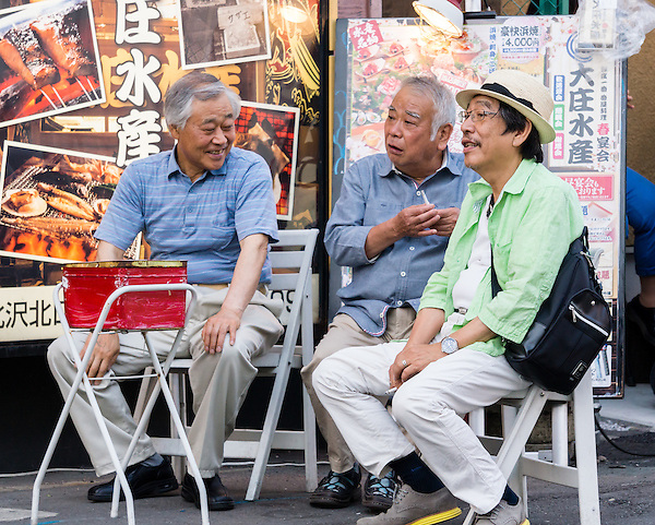"""Three oyaji are talking in a smoking area. Oyaji means """"old man"""" in Japanese. These men are most likely retired. They are enjoying a warm summer evening with some talk and cigarettes."""